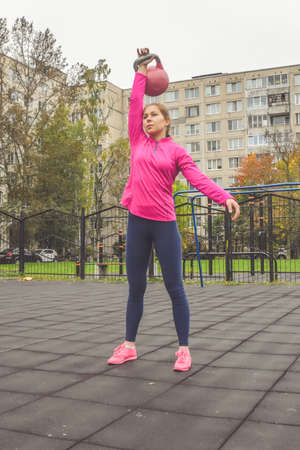 the young beautiful girl doing sports exercises kettlebell fitness outside Imagens