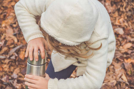 A child with a insulated bottle on fallen leaves