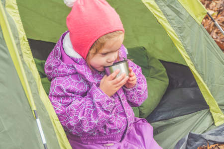 the on an autumn day a child is having Breakfast in a tent at a campsite