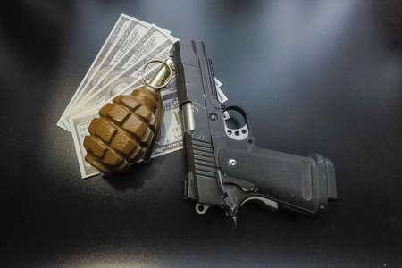 the black background a pistol and a hand grenade