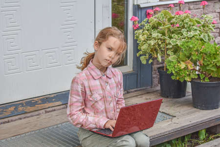 a girl child with a laptop is sitting on the porch of the house during a lesson on a remote photo without a filter