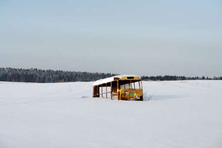 unneeded: Frame of old bus in field in winter