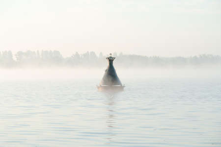 Rocking on waves of buoy in river in fog creates calm atmosphere photo