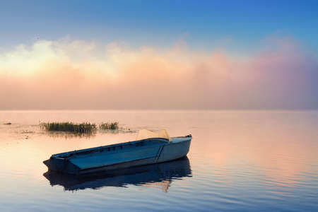 Large frontal cloud of mist at sunrise and a small fishing boat photo