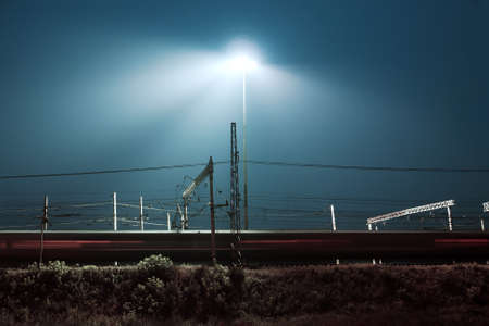 Night express train hurtling at high speed past Stock Photo