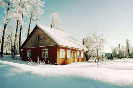 yule log: Snowy hills in Russian countryside in morning. Red wooden house windows turned to east. Stock Photo