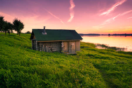 Little lone house on banks of the river at sunset in silence