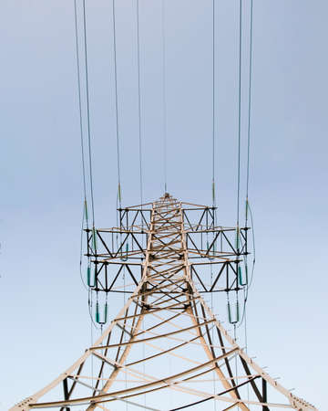 Lonely metal mast power lines with wires standing vertically from below against a blue sky day. Stockfoto