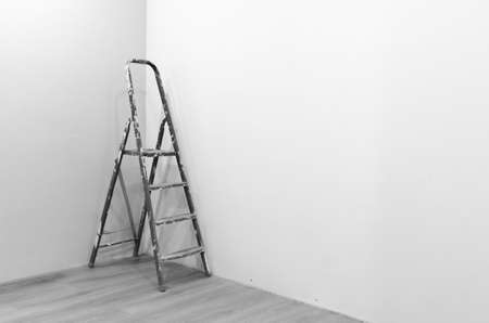 Black-and-white photograph of a ladder to repair a stained white paint standing in the corner of a freshly painted room on the new floor. Stok Fotoğraf