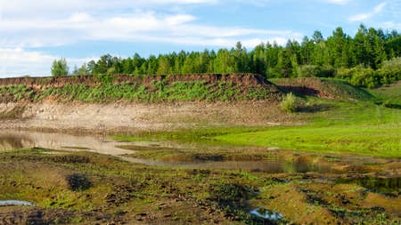 Small channels and water of the river at a steep hill with a forest in the far North in the taiga of Yakutia.