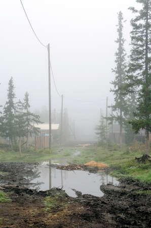 Eine große Pfütze auf der Dorfstraße im Morgennebel zwischen Bäumen und Häusern mit Zäunen und Drähten im Norden Jakutiens. Standard-Bild