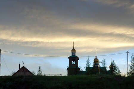 A wooden Church with Golden domes stands at sunset under the fat sky on a hill in the Northern village of Yakutia Suntar.