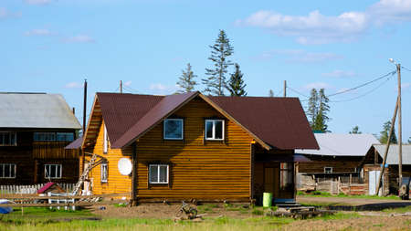 A new private cottage of yellow logs, among the old village houses, is being completed in the summer in Yakutia in the village of Suntar.