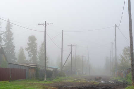 The street of the Northern Yakut village of ulus Suntar in the morning fog with puddles on the road and standing car behind the power line poles and wires.