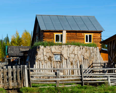The room for cattle khoton, made of cow dung and wood, overgrown with grass stands on a plot with a house made of pine in the North of Yakutia.