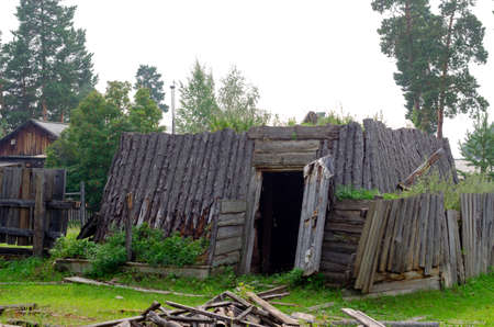 The room for cattle khoton, made of cow dung and wood, overgrown with grass stands with an open door on the grass in the village of Yakutia.