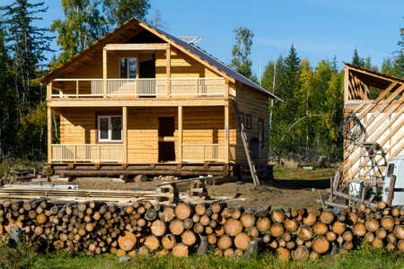 A new private residential building made of yellow pine logs stands unfinished among spruce forests and firewood for burning wild forest in the tundra of Yakutia, in the recently developed territory in the village of ulus Suntar.