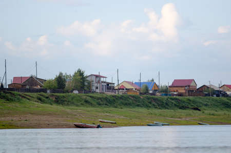 Boats are on the banks of the river Viluy at the cliff with the houses of the village of ulus Suntar in the North of Yakutia in Russia.