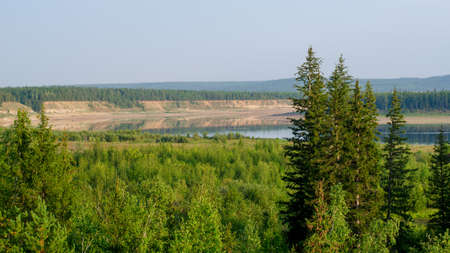 View of the turn of the Northern Yakut river vilyu reflected among the steep banks of the hills and spruce forest on the mountain with trees in the foreground. Stockfoto