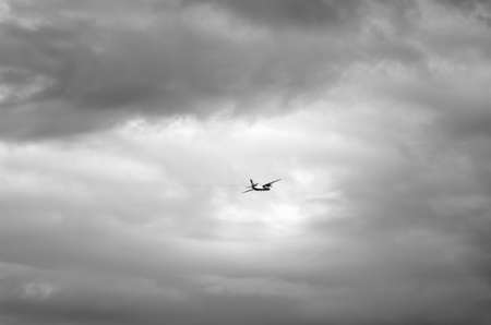 Black and white photo of a dangerous airplane flying in dark clouds high in the sky. Stockfoto