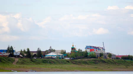 The road from the boats on the river Bank leads to the cliff with houses and silhouettes of cars going to the Church among the houses in the Northern village of ulus Suntar in Yakutia.