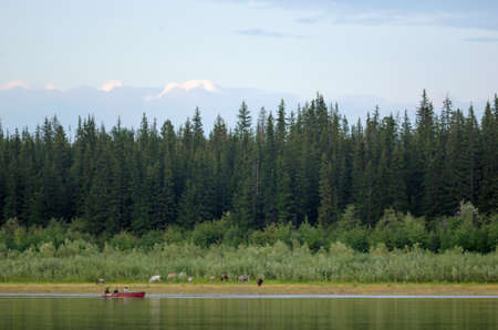Three vague silhouettes of people of the Northern Yakuts on a boat with oars floating across the river vilyu against the shore with horses and spruce forest taiga. Stok Fotoğraf