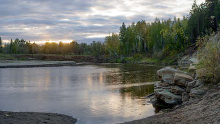 Bright sunset with reflection in the water of a small river Kempendyay in Yakutia between the cliffs and spruce forests in the wild North.