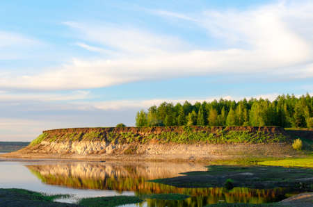 The steep slope of the shore with different soil clay and sand from the Northern rivers of Yakutia, the Vilyuy bright day in the tundra.