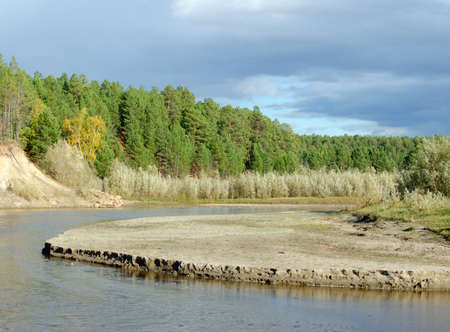 Erosion erosion of the sandy shore of a small Northern Yakut river in the wild Northern taiga in a picturesque spruce forest.