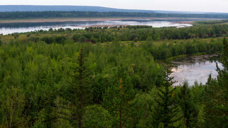 Overgrown with fir-trees and shrubs of the Northern shore of the river in Yakutia, the Vilyuy with a lake in the impenetrable taiga.