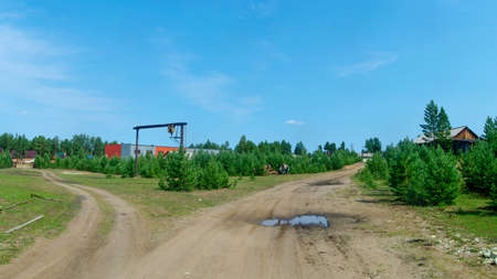 Fork of the road to residential village houses and working area in the Northern village of Yakutia on the background of spruce forest tundra.