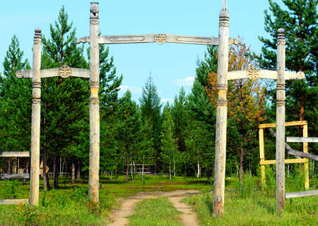 Yakut entrance to the Park in the wild far North with religious symbols of the local faith, pillars and tree of life.