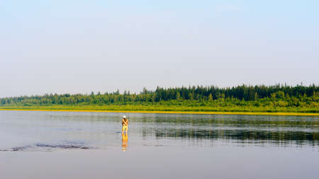 Yakut girl tourist fisherman fishing spinning standing in the water with his pants rolled up on the shoals of the Northern river vilyu and tundra spruce forest. Stock fotó