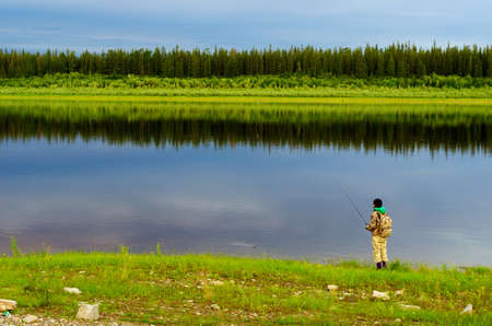 Yakut girl tourist angler with a backpack pulls out a spinning bait with the grass from North of the Vilyui river on the background of wild taiga forests. Stock Photo