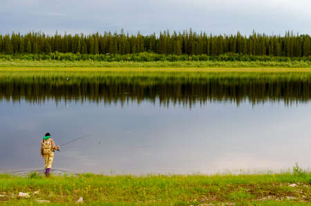 Yakut girl tourist fisherman with a backpack in boots comes into the Northern river vilyu with a spinning in his hand in the background of the wild forest taiga.
