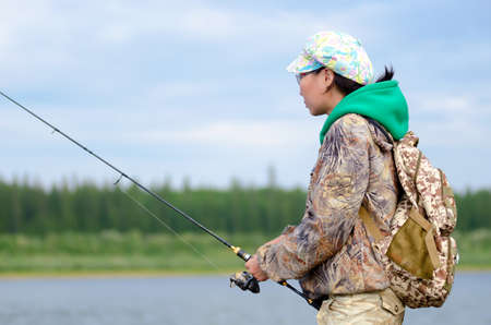 Yakut girl-tourist fisherman looking at the fishing rod spinning on the shore with a backpack in a cap on the river vilyu and tundra spruce forest.