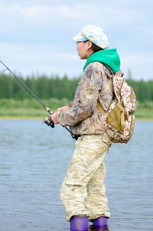 Yakut girl-tourist fisherman looking at the fishing rod fishing spinning on the shore with a backpack in a cap and boots on the river vilyu and tundra spruce forest.