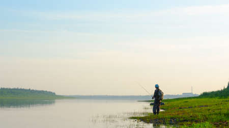 Yakut Asian girl tourist fisherman with a backpack and a cap to fish in the river vilyu in the haze at sunset in the wild North of Russia on the background of the village Suntar.