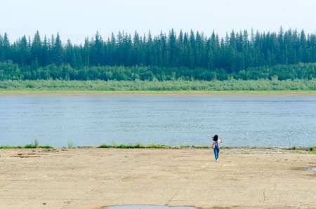 Girl tourist with a backpack , briskly goes one to a concrete cliff on the shore of the old pier at the Northern river vilyu with spruce tundra forests of Yakutia on the other side. 写真素材 - 132247162