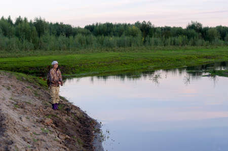 Yakut Asian girl-the tourist-fisherman with a backpack is fishing on the river Kempendyay from the sandy hills of the wild North spruce tundra of Russia.