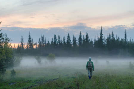 A tourist girl with a backpack goes into the fog in the forest in the evening at sunset in the wild taiga of Northern Yakutia in Russia. Stock Photo