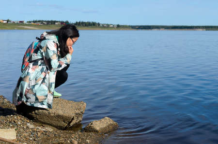 Modern sad girl Yakut looks at the water of the river vilyu contaminated with waste from diamond production in the North of Russia in Yakutia in the village of Suntar.