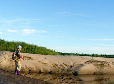 Yakut Asian girl-the tourist-fisherman with a backpack is fishing on the river Kempendyay sandy hills in the wild North of the taiga of Russia.