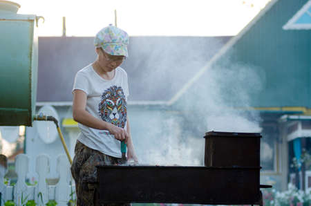 Yakut Asian girl with glasses and a cap is preparing a barbecue at a large grill in the smoke on the background of a residential private house and a water pump in the North of Yakutia.
