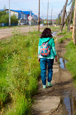 Yakut sporty girl with backpack light walk goes along the old sidewalk North of the village Suntar.