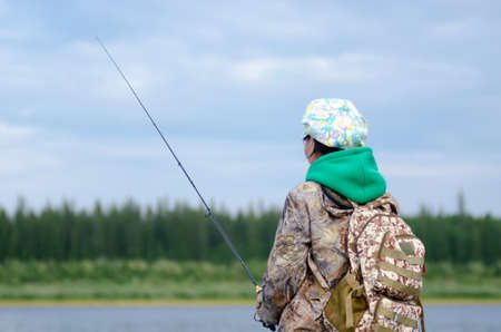 Yakut girl tourist fisherman fishing spinning on the shore with a backpack in the cap of the river Viluy and tundra spruce forest. Imagens