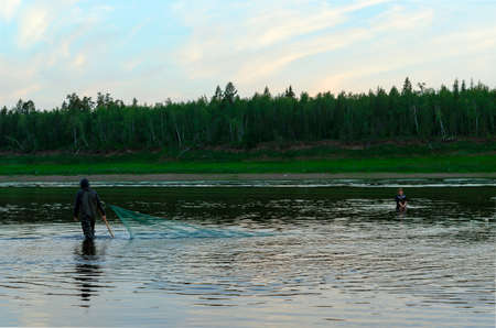 Two men Yakuts go in wading boots with fish net on the wildlife in the river Vilyuy in a forest taiga traditionally catching the local fish tugun.