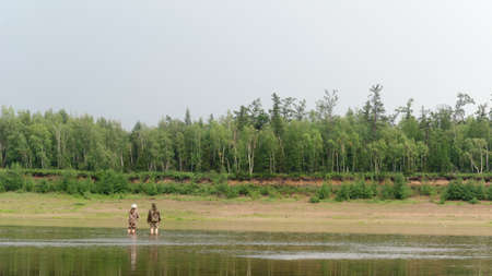 Two Yakuts a young girl and a man talking, standing in the river with a angling rod, teaching modern fishing spinning on the background of the forest taiga.