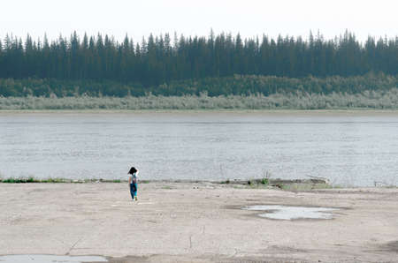 Girl traveler with backpack goes to the edge of the concrete sidewalk touching the hair on the Bank of the old pier North of the river vilyu with spruce forests and the tundra of Yakutia on the other side.