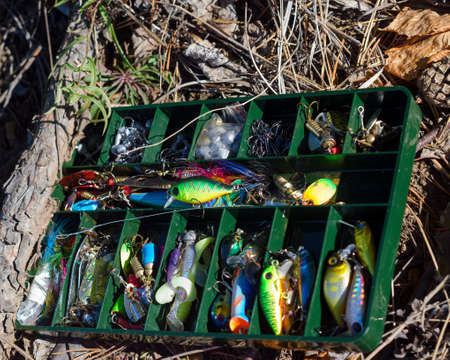 Small fishing lures for microjig and spinning with lures, rubber lures and hooks lying on the ground with spruce needles in the forest.